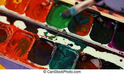 Man mix gouache paint with paintbru