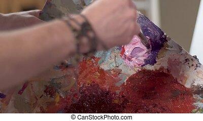 Man Mixes Paints on Palette - Man mixing paints on palette,...