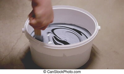 Man mixing two paint colors in bucket