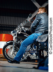 Man motorcyclist in leather clothing on his motorbike