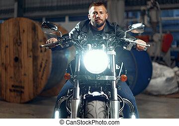 Man motorcyclist sitting on his motorbike in underground parking