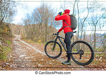 Man mountain biking rests and drinks from the canteen