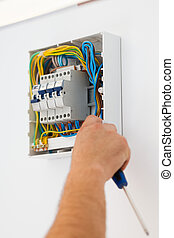 Man Mounting Electric Fuse - Electrician man with...