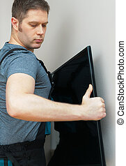 Man mounting new TV on the wall.