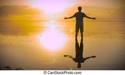 Man moves into lotus pose on beach reaching out towards the sun