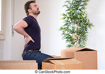 Man moving boxes and feeling back pain because heavy weight