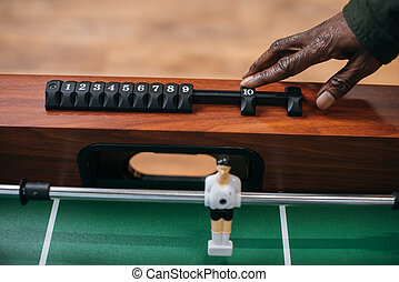 man moving counter on table football - cropped shot of...