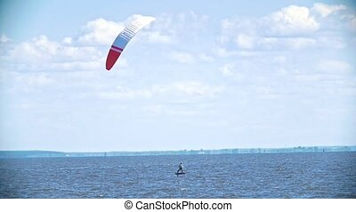 Man moving on the water with a sail on a kitesurf, slow...