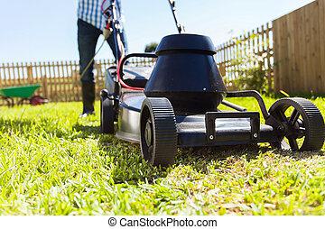 man mowing house garden lawn