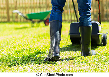 back view of man wearing gumboots mowing home garden lawn