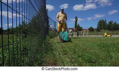 Man mows backyard lawn with electrical mower machine. Gimbal...