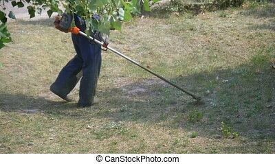 Man mows grass using a portable lawnmower