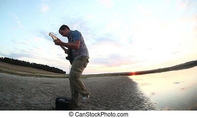 man musician nature stands sideways at sunset near the lake plays the electric guitar evening sun sets Video