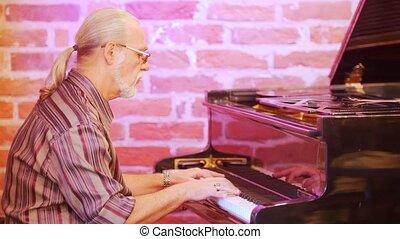 Man musician playing the piano. He's wearing a plaid shirt,...
