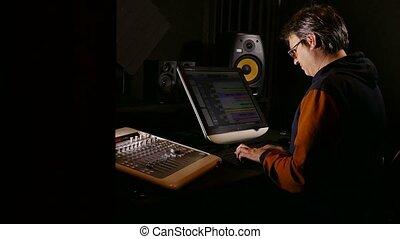 man musician sound designer in his recording studio -...