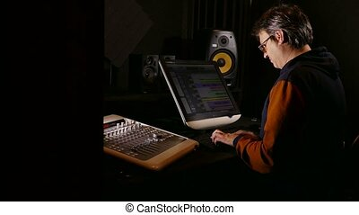 man musician sound designer in his recording studio -...
