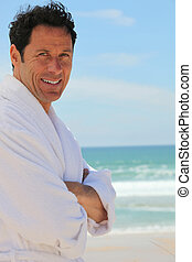 Man n dressing gown stood on beach