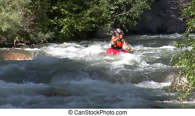 man navigates white-water rapids in kayak