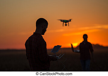 Man navigating drone above farmland