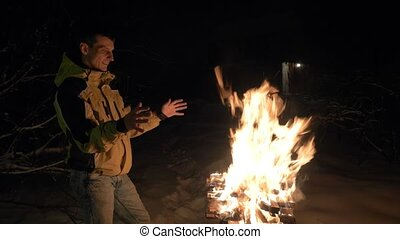 Man near brazier with fire and heats his hands in winter.