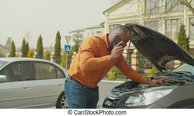 Man near broken car calling for roadside assistance - ...
