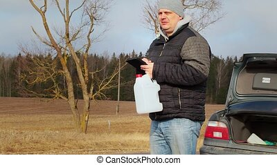 Man near car looking for informatio