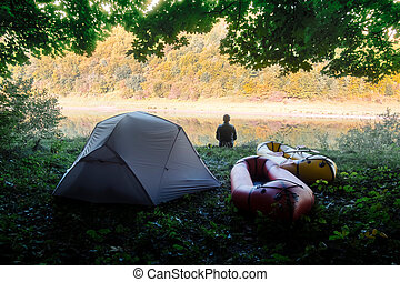 Man near tent and packrafts in forest camp
