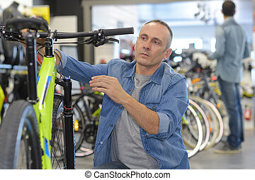 man next to bicycle in showroom