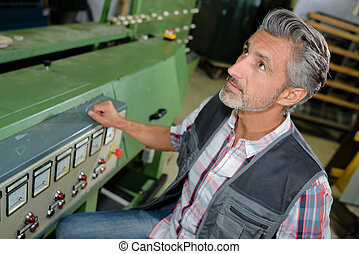 Man next to machine overseeing production
