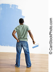 Man observing paint job. - African American young man...
