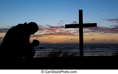 Man Of Prayer - Man praying by a cross at the beach while...