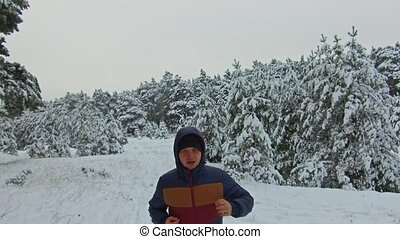 man of young runner Sportsman Running Through Snowy Forest. shot front view winter tree forest in the snow