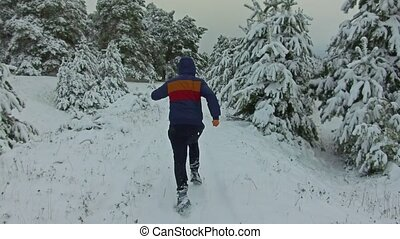 man of young runner Sportsman Running Through Snowy Forest. shot front view winter tree forest in the snow outdoors