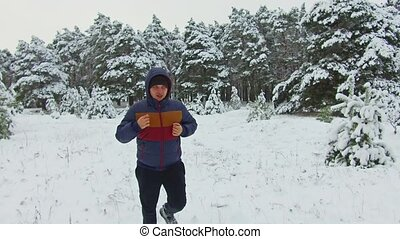 man of young Sportsman runner Running Through Snowy Forest. shot front view winter tree forest in the snow
