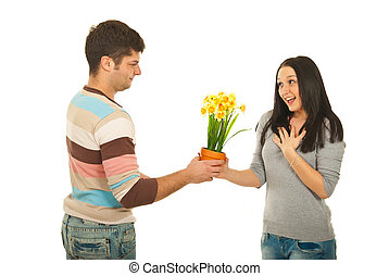 Man offering flowers to amazed woman