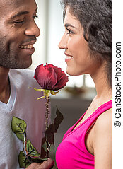 Man offering rose to his pretty girlfriend. african man looking at indian woman and smiling