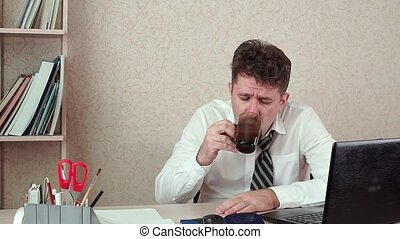 Man office Manager has a headache. He's sitting at his laptop with coffee.