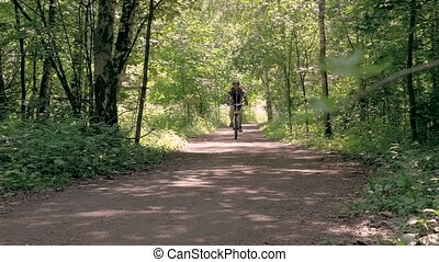 Man on a bicycle in summer in a park. slow motion