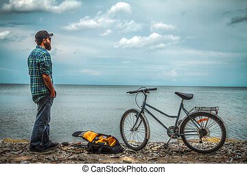 man on a bicycle near the sea.