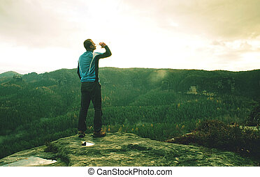Man on a cliff edge on top of mountain with gorgeous view