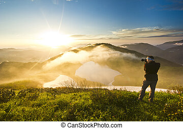 man on a hill at sunset with camera making photo