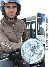 Man on a moped with a bus in the background