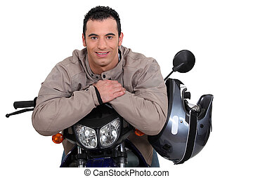 Man on a motorbike with his helmet on the side