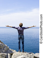 man on a mountain with open hands towards the word, blue sky end sea, freedom concept and travel