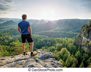 Man on a stone observing the landscape. Young sportsman