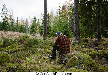 Man on a stump in the forest