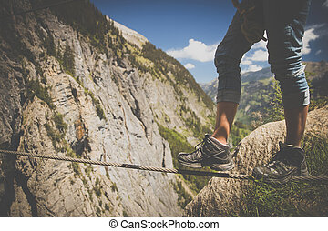 Man on a via ferrata, walking on an iron rope. Kandersteg