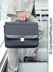Man on an escalator holding a briefcase