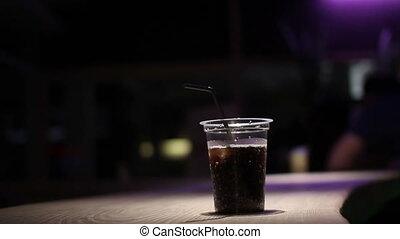 man on bar drink coke from plastic glass