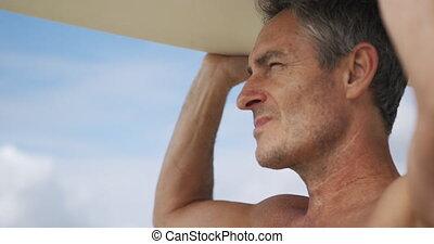 Man on beach with surfboard